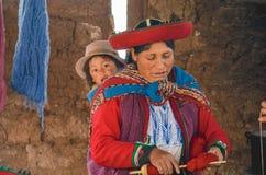 CHINCHERO, PERU 3 JUNI, 2013: De inheemse Cusquena-vrouw kleedde zich in traditionele kleurrijke kleding verklarend de vervende d Stock Afbeeldingen