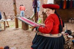 CHINCHERO PERU JUNI 3, 2013: Fungerar iklädda traditionella färgrika kläder för den infödingCusquena kvinnan på en vävstol utanfö Royaltyfria Foton