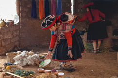 CHINCHERO, PERU 3. JUNI 2013: Gebürtige Cusquena-Frau kleidete in der traditionellen bunten Kleidung die färbenden Threads und un Lizenzfreie Stockbilder