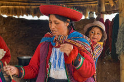CHINCHERO, PERU 3. JUNI 2013: Gebürtige Cusquena-Frau kleidete in der traditionellen bunten Kleidung die färbenden Threads und un Stockbilder