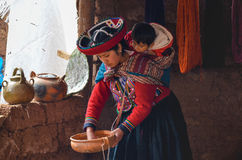 CHINCHERO PERU JUNI 3, 2013: Iklädda traditionella färgrika kläder för infödingCusquena kvinna som förklarar de färga trådarna oc Royaltyfri Foto