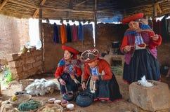 CHINCHERO PERU JUNI 3, 2013: Iklädda traditionella färgrika kläder för infödingCusquena kvinna som förklarar de färga trådarna oc Royaltyfri Bild
