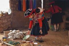 CHINCHERO PERU JUNI 3, 2013: Iklädda traditionella färgrika kläder för infödingCusquena kvinna som förklarar de färga trådarna oc Royaltyfria Bilder