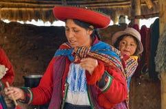 CHINCHERO PERU JUNI 3, 2013: Iklädda traditionella färgrika kläder för infödingCusquena kvinna som förklarar de färga trådarna oc Arkivbilder