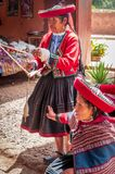 Peruvian woman in Chinchero. Chinchero, Peru - March 9, 2015: Peruvian woman dressed in traditional clothes while working on a homemade wool industry using royalty free stock image