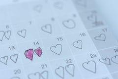 Chincheta escrita niña del corazón en la fecha de la tarjeta del día de San Valentín del 14 de febrero Imágenes de archivo libres de regalías