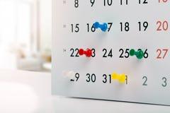 Chinchetas en el calendario - concepto de horario ocupado Foto de archivo libre de regalías