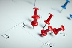 Chinchetas rojas en calendario Fotos de archivo libres de regalías