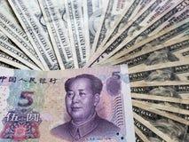 Chinees bankbiljet van vijf yuans en achtergrond met Amerikaanse dollarsrekeningen