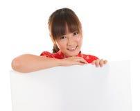 Chinees cheongsammeisje die wit aanplakbiljet houden Stock Foto's