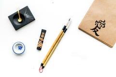 Chinees of Japans kalligrafiepatroon Hiëroglief in ambachtdocument notitieboekje en het schrijven toebehoren op witte achtergrond royalty-vrije stock afbeelding