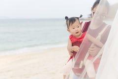 Chinees mamma en meisje in de vakantie van de babydrager op strand royalty-vrije stock fotografie