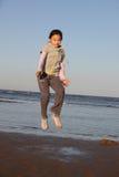 Chinees meisje dat op het strand springt Stock Fotografie
