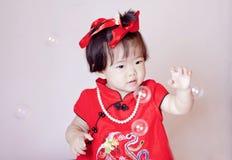 Chinees weinig baby in de rode zeepbels van het cheongsamspel Stock Fotografie