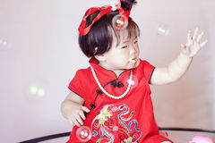 Chinees weinig baby in de rode zeepbels van het cheongsamspel Royalty-vrije Stock Foto