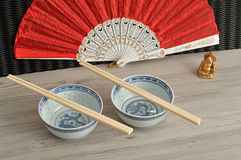 Chines bowls, chopsticks, a hand fan and a Buddha Stock Images