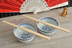 Chines bowls, chopsticks, a hand fan and a Buddha Royalty Free Stock Photos