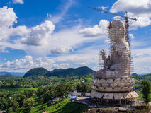 Chinese angle statue in mountain view under cloudy blue sky. In Thai temple Stock Photo