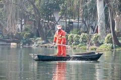 Chinese arbeiders schoonmakende bladeren van het meer met de hand, dag, boot, status Stock Foto