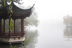 Chinese arbor in the park. Traditional Chinese gazebo on a lake in the fog Royalty Free Stock Image