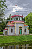 Chinese arbor in spring park. Chinese pavilion with dragon sculpture on the roof in Ekaterinisky park of Tsarskoe Selo (Pushkin), St. Petersburg, Russia Stock Photography