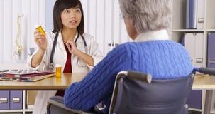 Chinese arts die over medicijn aan bejaarde patiënt spreekt stock foto's