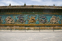 Chinese Asia, Beijing, Beihai Park, ancient buildings, nine dragon wall. Both sides fired by glazed brick red yellow blue white green purple color 18 dragons stock photography