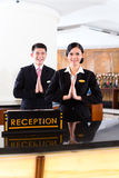 Chinese Asian reception team at hotel front desk. Chinese Asian reception team at luxury hotel front desk welcoming guests with typical gesture, a sign of good Royalty Free Stock Photo