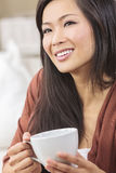 Chinese Asian Woman Drinking Tea or Coffee. A beautiful happy young Chinese Asian Oriental woman with a wonderful toothy smile drinking tea or coffee Stock Images