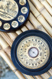 Chinese Astrology. Feng Shui compass on bamboo background showing ba gua wheel with trigrams and Chinese astrology animal signs engraved on ivory bone royalty free stock photo