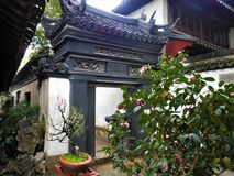 Chinese atmosphere and plants, art, history and architecture in Shanghai city, China. Enchanting roof, trees, beautiful entance and nature, tradition and stock photo