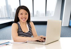 Chinese Aziatische vrouw die en op haar laptop bij het moderne bureau van de bureaucomputer werken bestuderen Royalty-vrije Stock Afbeelding