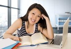 Chinese Aziatische vrouw die en op haar laptop bij het moderne bureau van de bureaucomputer werken bestuderen stock afbeelding