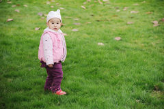 A chinese baby. Is standing on the grass Stock Photo