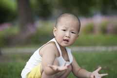 Chinese baby asking question on the grassland Royalty Free Stock Photo