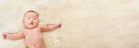 Chinese baby boy. Laying naked of fur bed with lot of copy space area on the right side Stock Photo