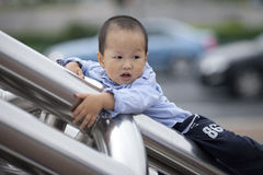 Chinese baby boy climb the ladder. Outiside stock image