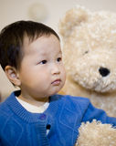 Chinese baby boy playing with a bear toy Royalty Free Stock Photo