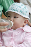 Chinese baby drinking water. In the park Stock Photos