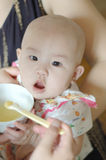 A chinese baby eating solid food from a spoon Stock Photo