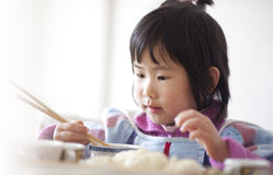 Chinese baby girl eating food with chopsticks Stock Photography
