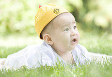 A Chinese baby on grass. A Chinese baby is looking forwards on grass with a cap on head outdoor Stock Photos