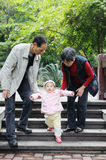 Chinese baby learn to walk. Grandma grandpa and grandchild Stock Photos