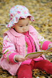 Chinese baby reading book in autumn Royalty Free Stock Photography