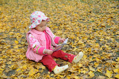 Chinese baby reading book in autumn Stock Photography