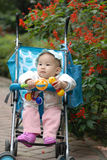 Chinese baby sitting in stroller with toys  Stock Photography