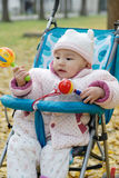 Chinese baby sitting in stroller with toys Royalty Free Stock Images