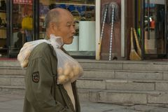 Chinese with bags of potatoes on his shoulder stock images