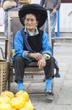 Chinese Bai Woman in Traditional Clothes. A Chinese ethnic minority Bai Zu woman sits in a chair as she sells gourds in Dali, Yunnan province, southern China Royalty Free Stock Images