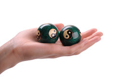 Chinese balls on a hand. Green Chinese balls for relaxation on woman hand on white background Stock Photos